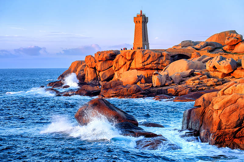 Lighthouse of Ploumanach Mean Ruz in Perros-Guirec on Pink Granite Coast, Brittany, France, on sunset