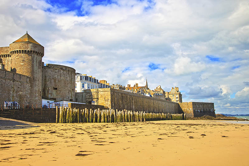 Saint Malo sand beach, city walls and houses. Low tide. Brittany, France, Europe.