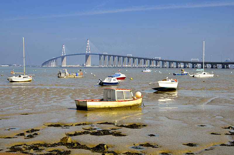 Small boats at low tide and the big bridge of Saint Nazaire at Saint Brevin les Pins in Pays de la Loire region in western France