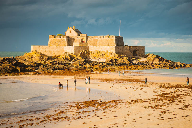 Saint-Malo, France - September 25, 2012: People stroll on the beach in front of an old fort in Saint-Malo, Brittany, France.