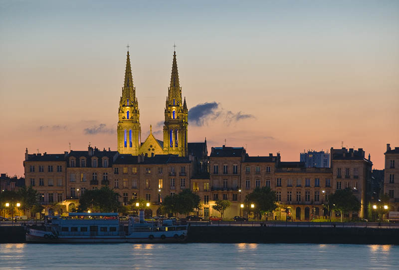 Lights of Quai des Chartrons reflecting in the Garonne river at dusk with the spires of St-Louis church behind. Bordeaux Gironde France.