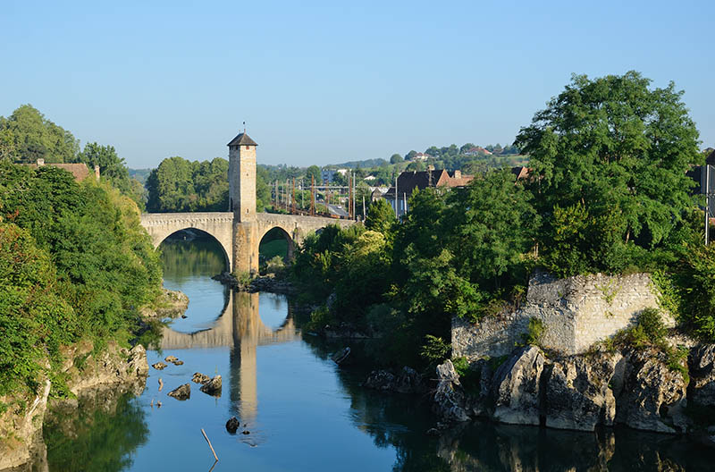 The river Gave de Pau is crossed by a 14th century bridge which has four arches and a tower. This is a landmark of the old French town Orthez.