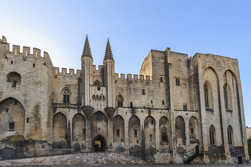 Avignon, France- June 10, 2014: The Palais des Papes is where the Pope John XXII moved the papal seat in 1316, and there it remained for the eight popes that followed. Not it is a museum.