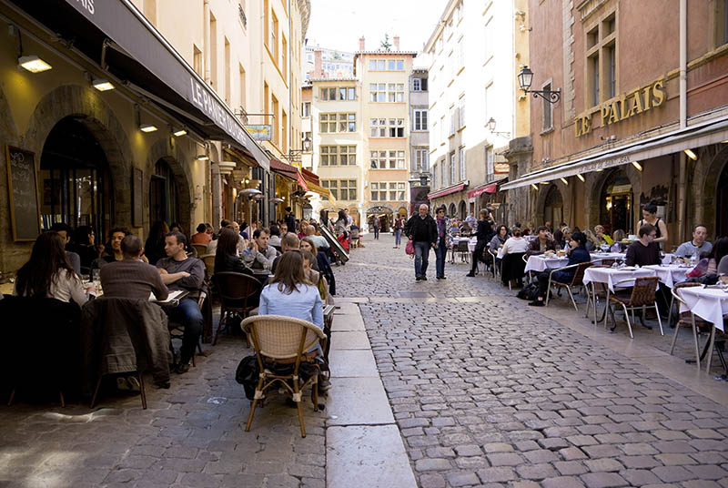 Lyon, France -- April 6, 2014: Street with traditional restaurants in Lyon, called Bouchon Lyonnais, which serve typical regional dishes. People are dining outside on a sunny April afternoon