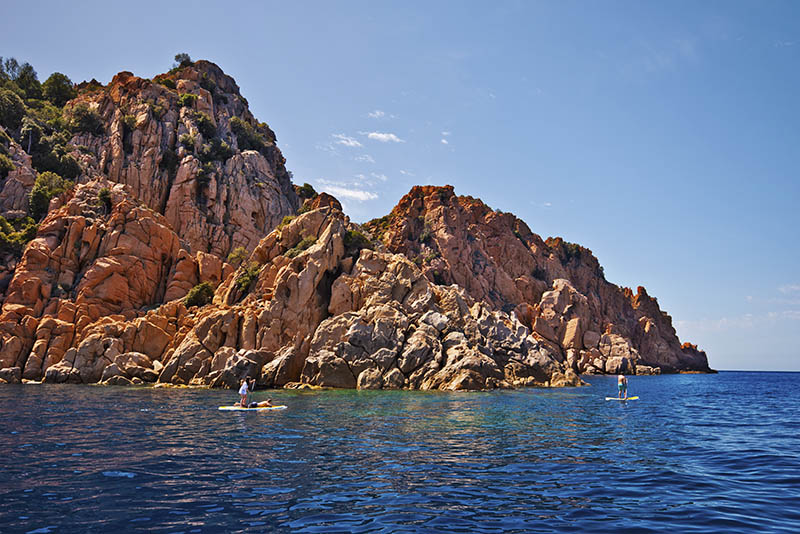 Piana, France – April 16, 2016. Magmatic vertical rocks of Calanques de Piana in Porto Bay of Corsica Island may be visited from Sea by means of Stand up paddle boarding, Corse-du-Sud