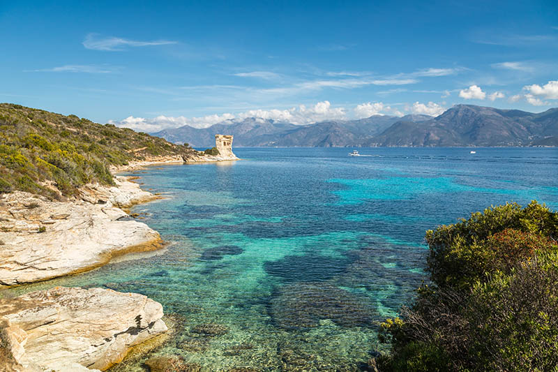 Ruins of the Genoese tower at Mortella with a turquoise mediterranean sea and rocky coastline of the Desert des Agriates near St Florent in Corsica with Cap Corse in the distance