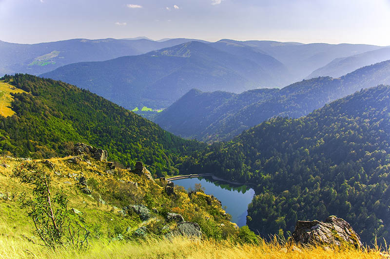 landscape panorama of the Ballons des Vosges Nature Park with lake Schiessrothried from Hohneck, Alsace, France.