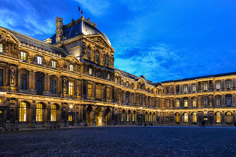 The Louvre is one of the most famous monuments and tourist attractions in Paris. This photo was taken during a spring evening after the sunset in the museum courtyard and features the grandoise architecture of the palace.