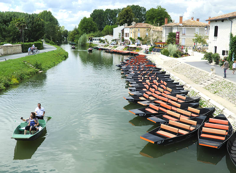 Coulon, France - July 27, 2011: Coulon, France. The image shows pleasure boats and a family of visitors rowing along the River Sevre in the village of Coulon in the Marais Poitevin region of France. The area is close to the city of Niort and is criss-crossed by waterways. It has therefore been named La Venise Verte (Green Venice). Coulon is known as the capital of the region and is a very popular with tourists.