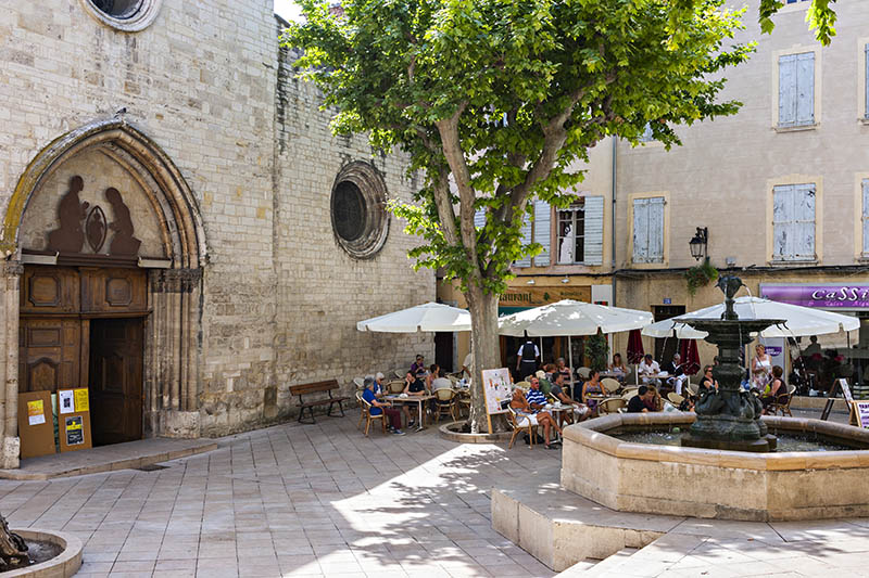 Manosque, Alpes de Haute Provence, France - June 26, 2010: daytime view of main square. On the left hand side the entrance of the cathedral, in the middle a fountain. In the background several locals and tourist having outdoor dining at local restaurants. Manosque. Alpes de Haute Provence. France.
