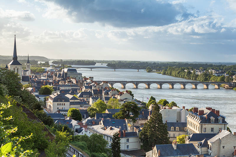 view of the French town of Saumur in the Loire River running through it