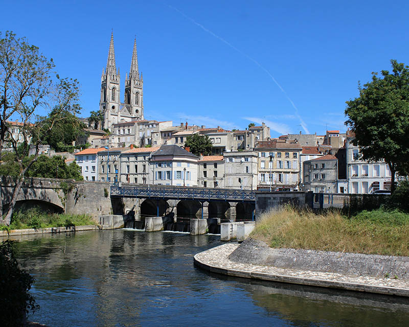 Niort, France, July 16 2017: A view of the historic town of Niort and St Andre's church, on the Sevre Niortaise River. Niort is large town in the Deux-Sèvres department in western France with a population of 60,000+.