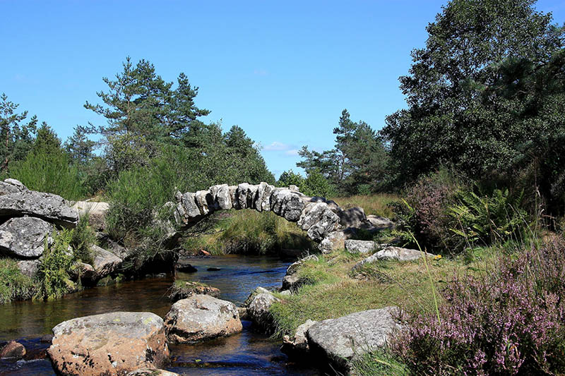 The Pont de Senoueix, Creuse, France, is a graceful arched bridge built of interlocked natural granite boulders which dates to the Gallo-Roman period and spans the Taurion river on a popular footpath used by hikers and ramblers