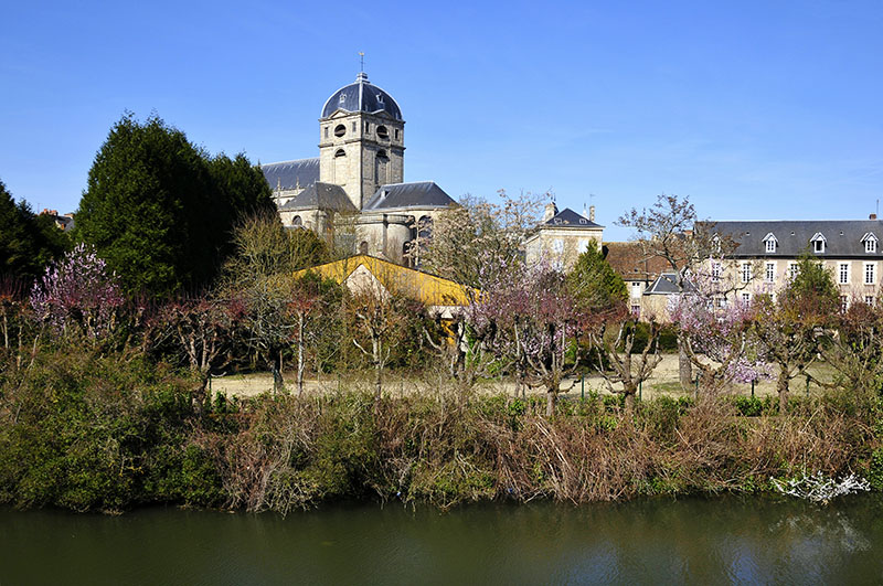 Sarthe river bank and bell tower of basilica Notre Dame at Alençon of the Lower Normandy region in France