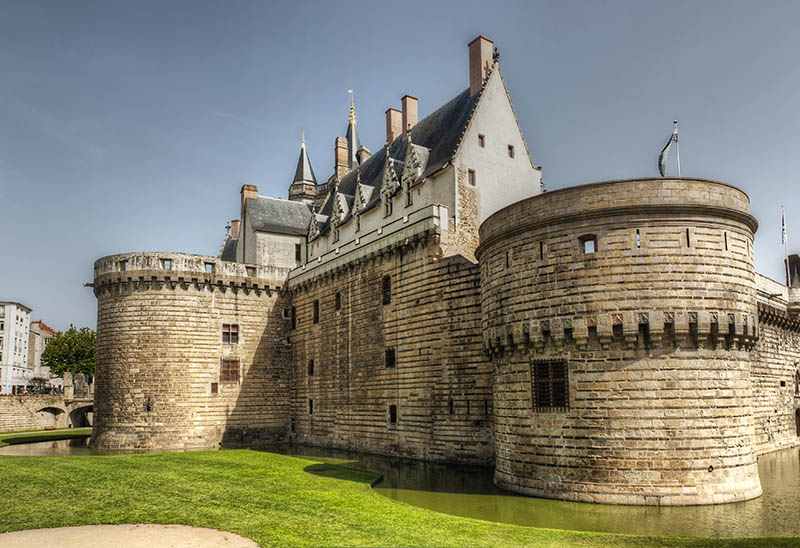 Nantes, France - August 20, 2011: Angle view of Castle of Brittany Duke's. Many tourists and some banners on the bridge . The castle now houses The Nantes History Museum.