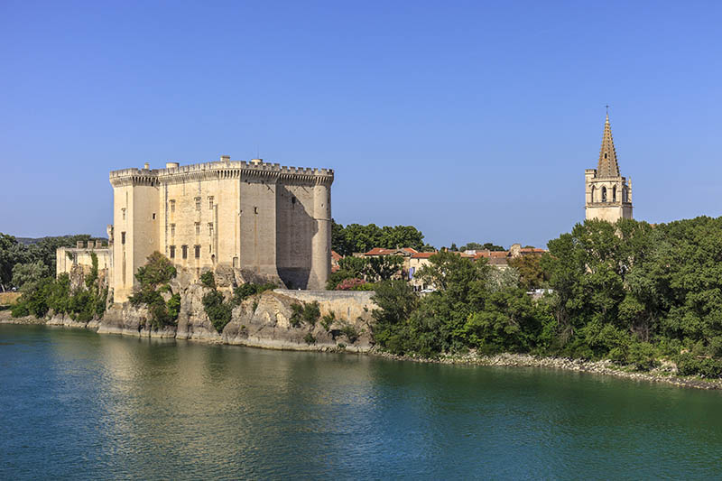 Tarascon, France - June 8, 2014: Image of Tarascon taken form the bank of the Rhone river. You can see the castle, the main sight of the town, a massive fortress built by the family of Anjou in the first half of the fifteenth century. Another landmark is the Église collégiale Ste Marthe (St Martha's Collegiate Church), built in the Romanesque style in 1197 and enlarged in the sixteenth and fifteenth in the Gothic style.