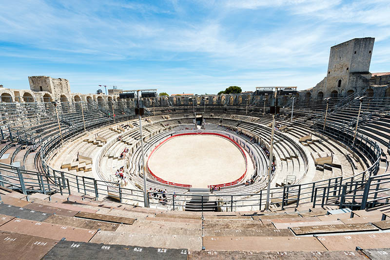 Arles, France - August 11, 2016: inside Arles historical arena. Some tourits sitting on tribune.