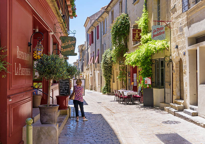 Woman looking at a restaurant menu in a picturesque street within the medieval town of Uzès, Nîmes, Gard, Occitanie, France.