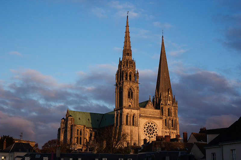 The sun sets on Chartres cathedral, east of Paris, France. The clouds are pink and the light illuminates the main stained glass window of the cathedral.