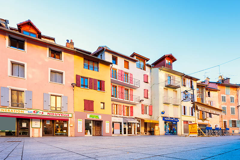 Stock photo of store fronts and colorful townhouses in downtown Gap, the capital and largest town of the Hautes-Alpes department of France