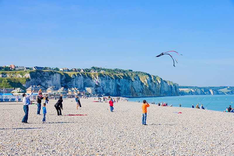 Dieppe, France - September 16, 2012: Beach scene, with kites, fishermen, locals and visitors, in Dieppe, France