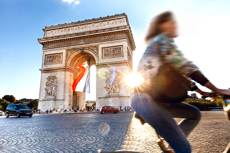 Arc de Triomphe in Paris with a big French flag under it