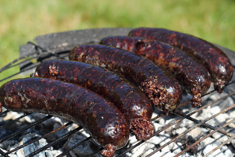 Grilling Blood Sausages on barbecue grill