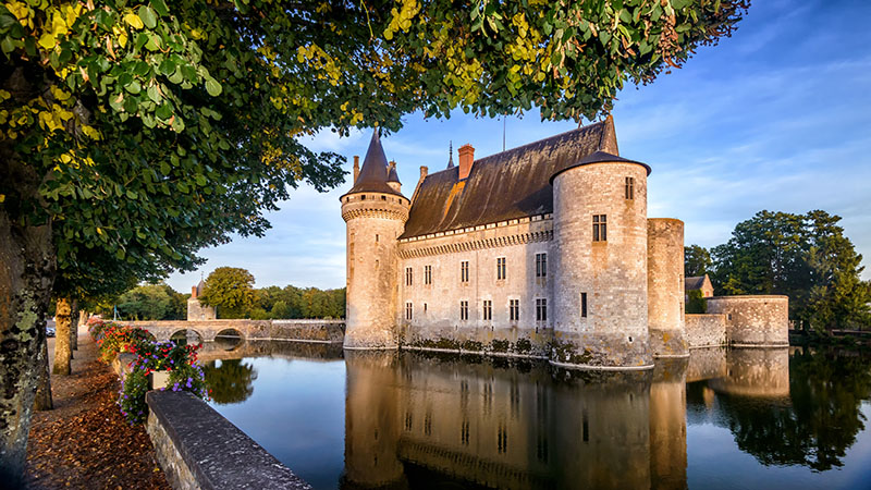 France - Sept 21, 2013: Castle or chateau de Sully-sur-Loire at sunset, France. This old castle is a famous landmark in France. Scenic panoramic view of the French castle on a river. Scenery of the medieval castle in summer.